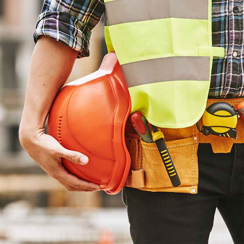 Construction worker holding a hard hat that should also have hearing protection while working.